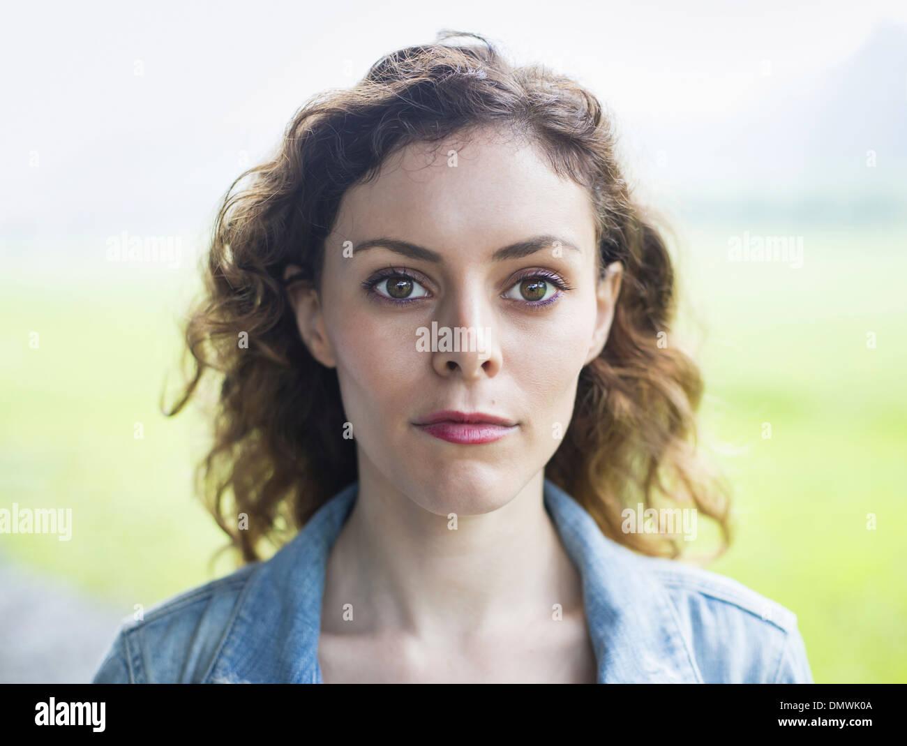 Eine junge Frau in einer ländlichen Landschaft mit vom Wind verwehten lockiges Haar. Stockbild