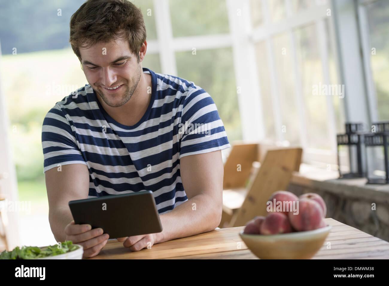 Ein Mann sitzt an einem Tisch mit einem digitalen Tablet. Stockbild