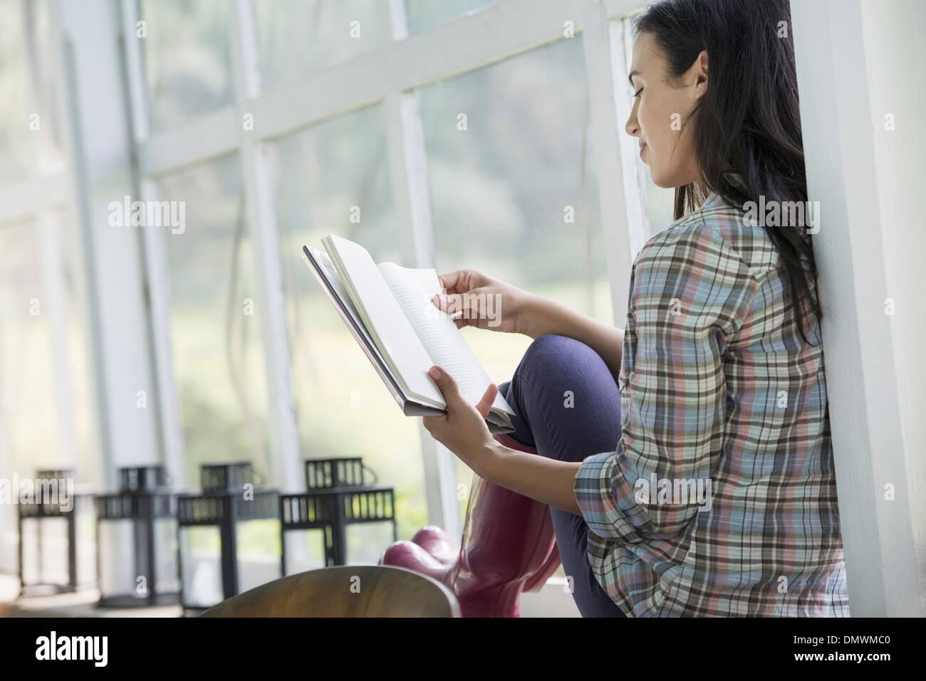 Eine junge Frau sitzt ein Buch zu lesen. Stockbild