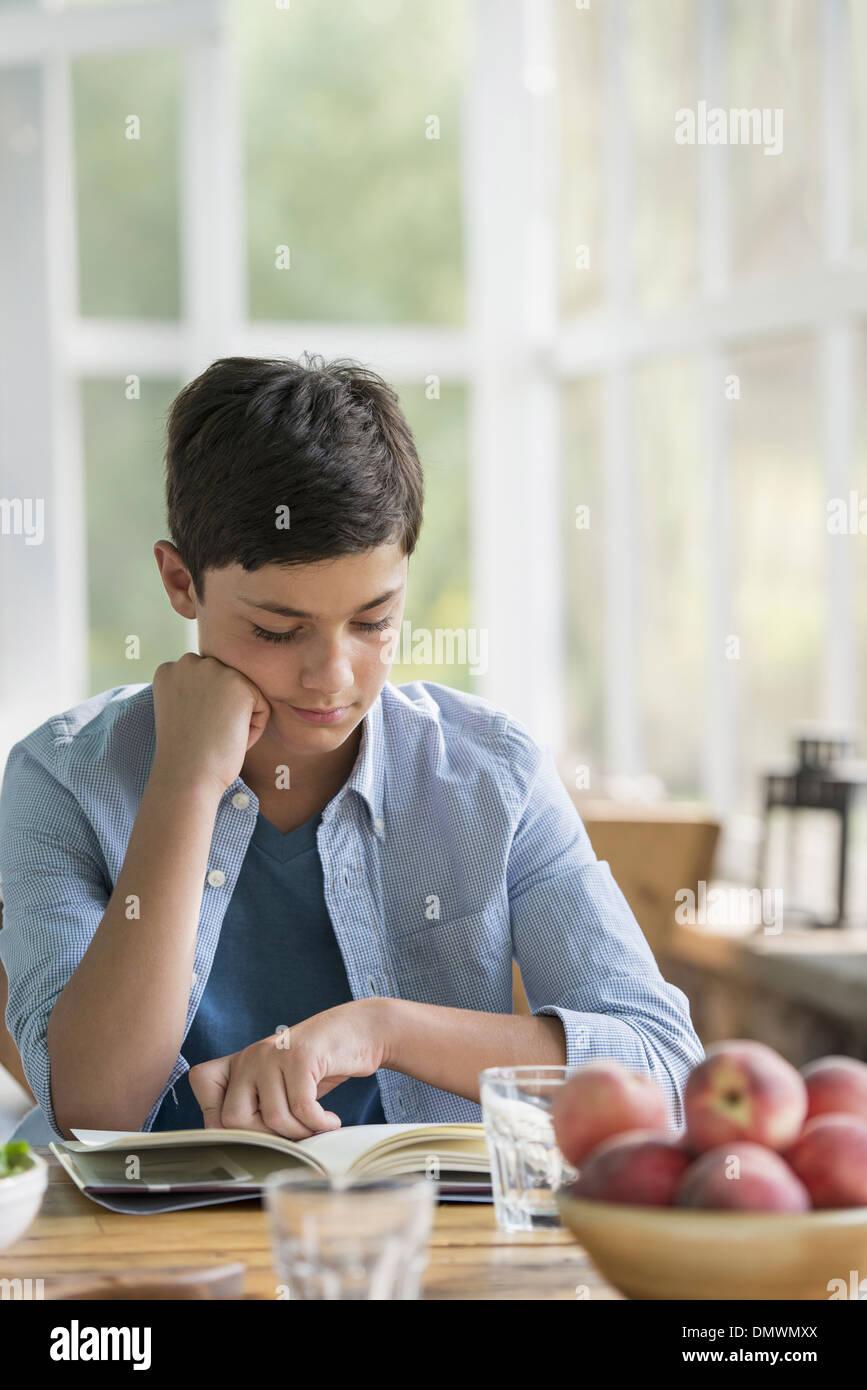 Ein kleiner Junge sitzt ein Buch zu lesen. Stockbild