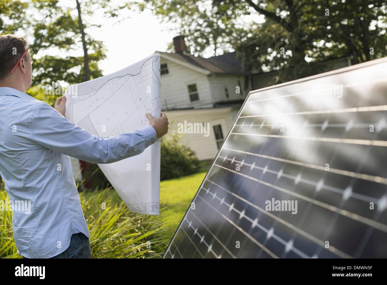 Ein Mann mit einem Plan, um ein Solar-Panel in einem Bauerngarten zu platzieren. Stockbild