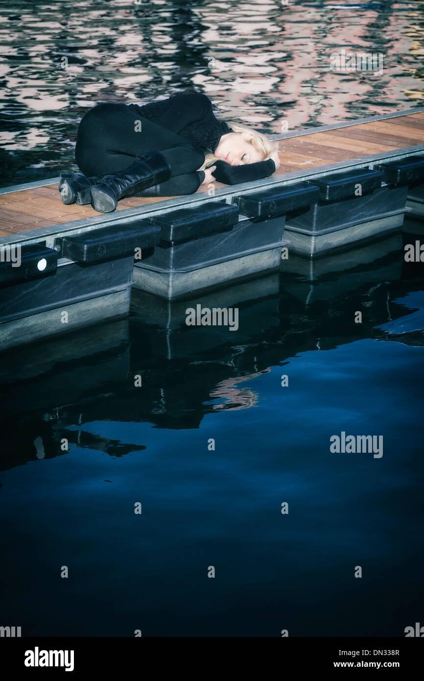 eine Frau in schwarzer Kleidung liegt auf einem Steg Stockbild