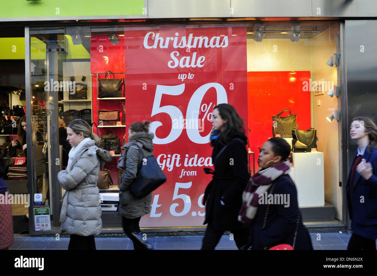 Frauen gehen vorbei an einen Shop mit einer Plakat-Lektüre ...