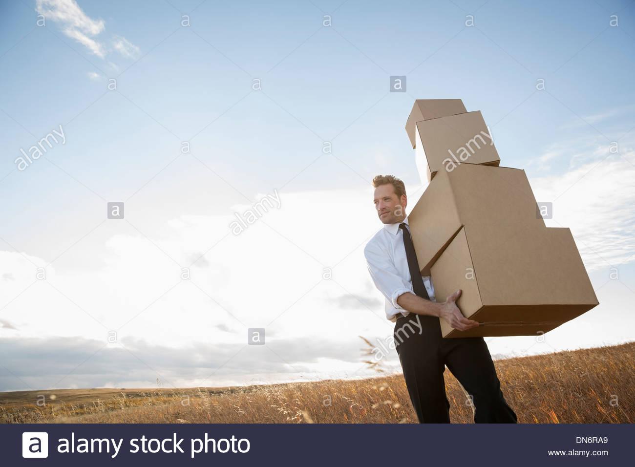 Geschäftsmann mit gestapelten Kartons Stockbild