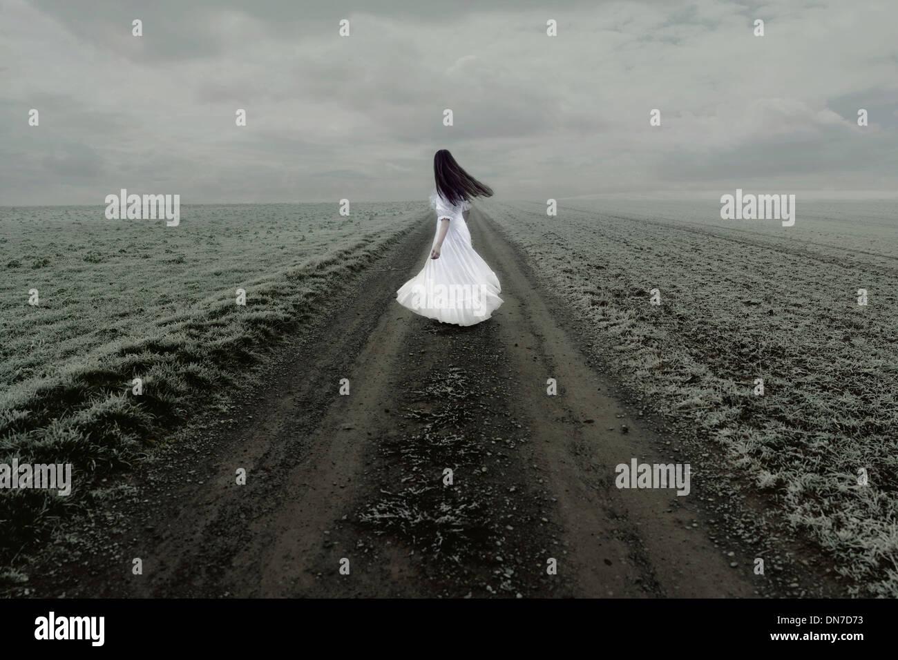 Frau in weißem Kleid steht allein auf einem Feldweg Stockbild