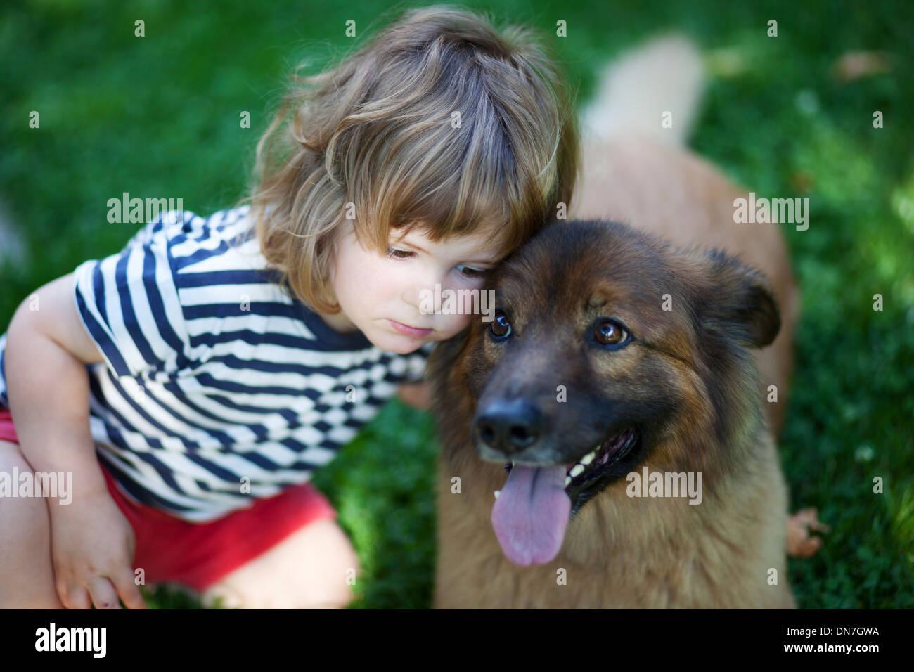 Kleiner Junge kuschelt mit Hund Stockbild