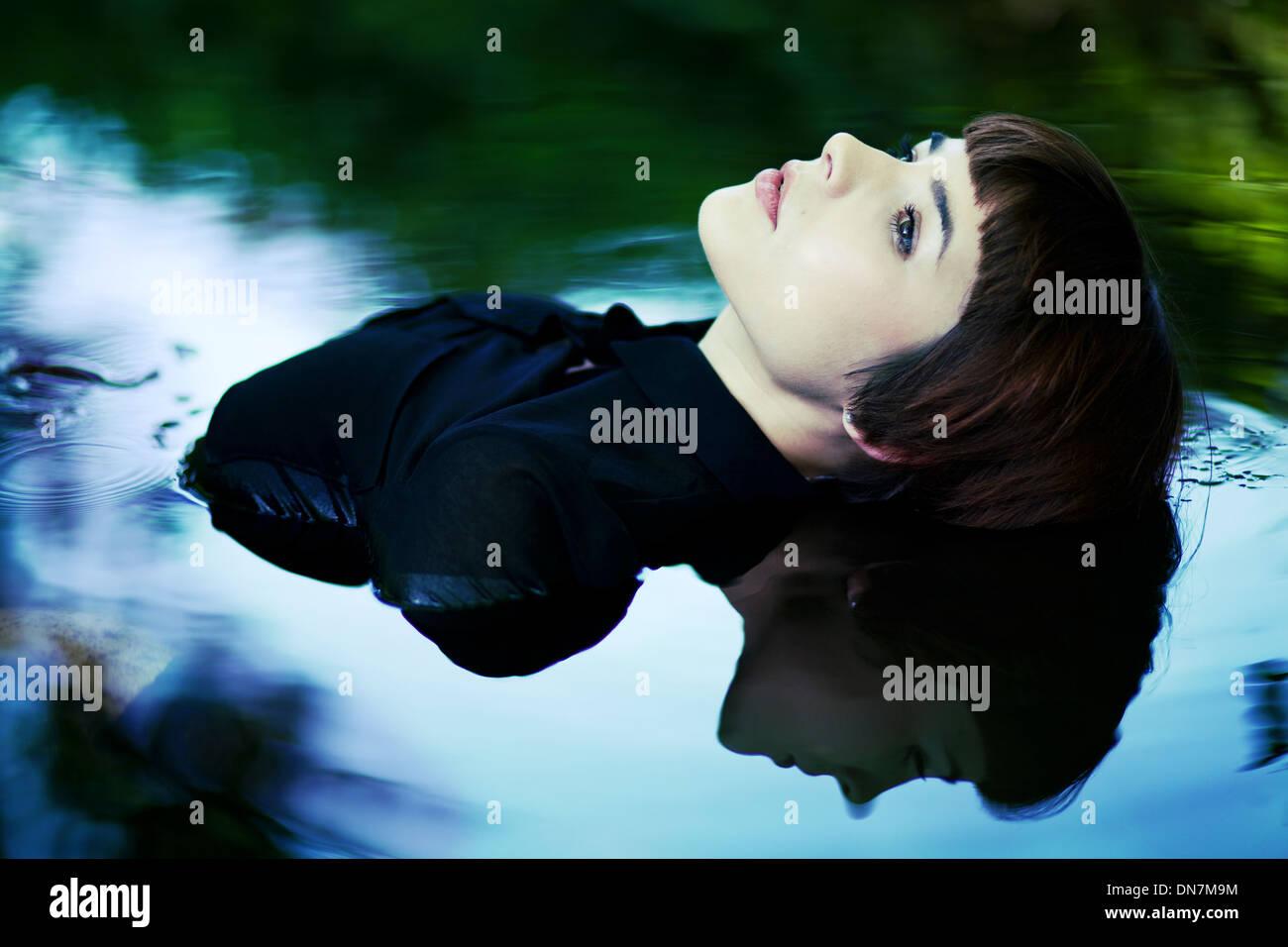 Junge Frau sitzt im Wasser, Porträt Stockbild