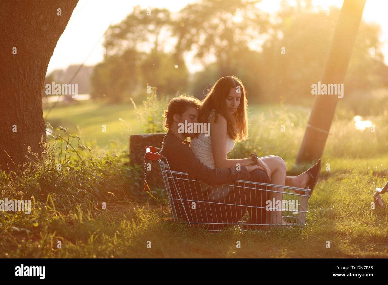 Liebespaar in einem Warenkorb bei Gegenlicht sitzen Stockbild