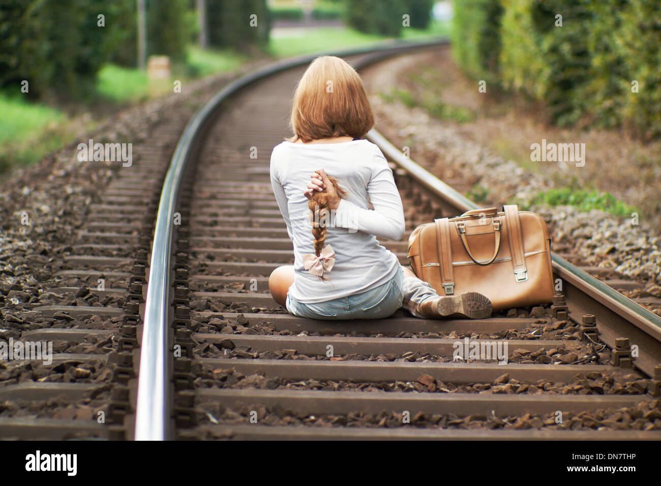 Frau sitzt auf der Bahnstrecke mit abgeschnittenen Zopf in der hand Stockbild