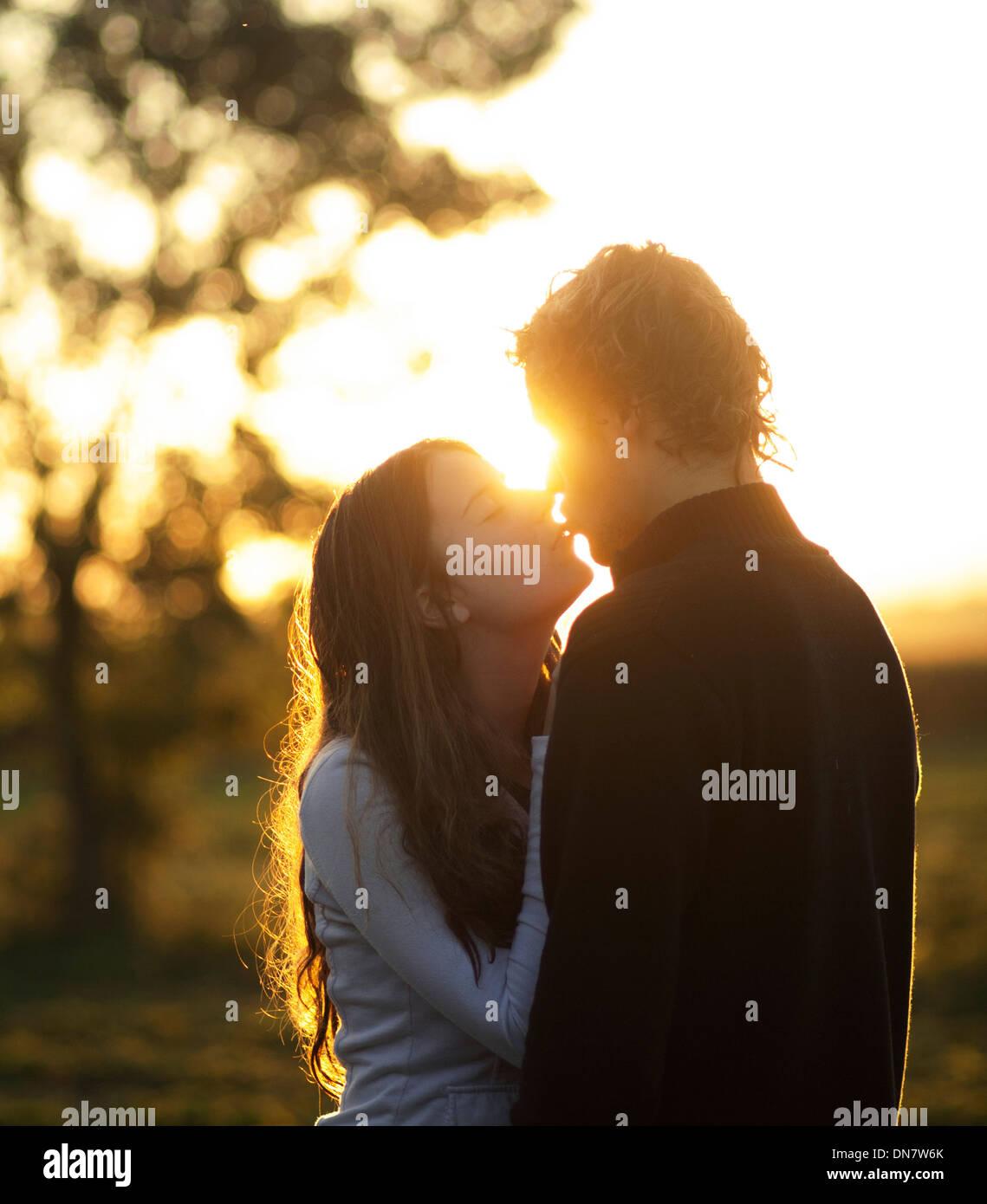 Liebendes Paar küssen bei Gegenlicht Stockbild