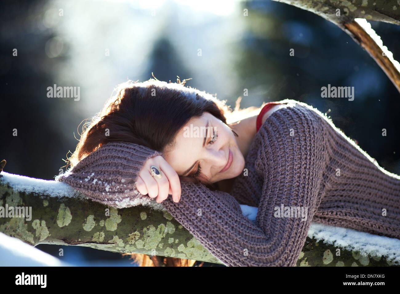 Junge Frau liegt auf einem Baumstamm im Schnee Stockbild