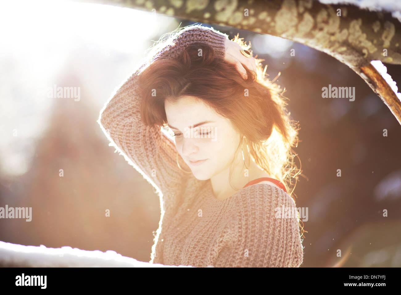 Porträt einer jungen Frau im Schnee bei Gegenlicht Stockbild