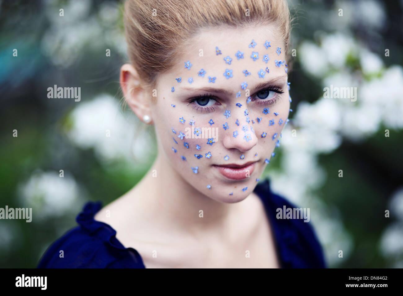 Porträt einer jungen Frau mit Blumen auf ihrem Gesicht Stockbild