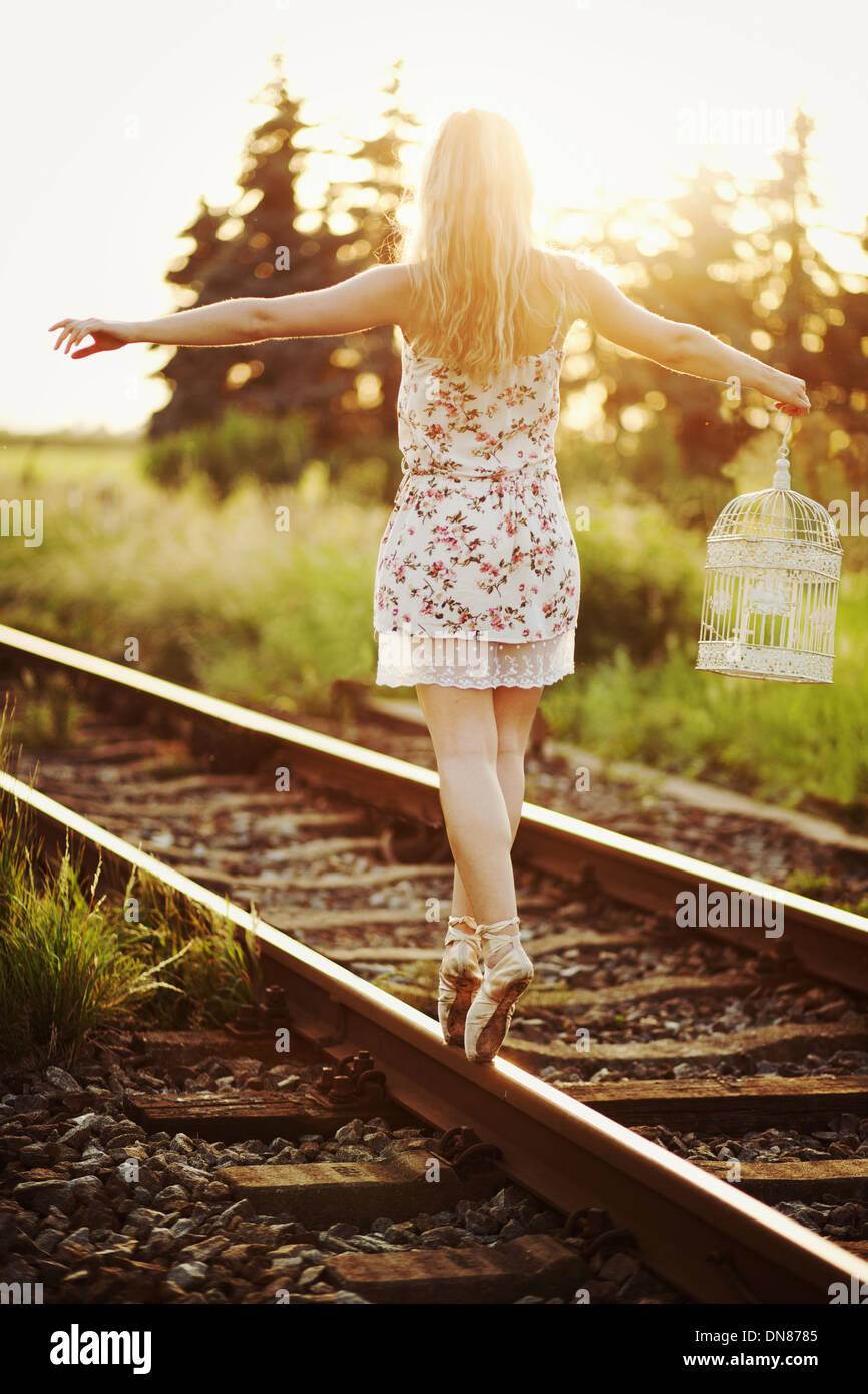 Junge Frau im Kleid, balancieren auf einem Gleis Stockbild