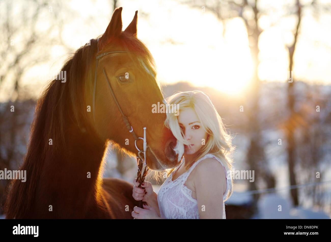Junge Frau im weißen Kleid mit Pferd im winter Stockbild