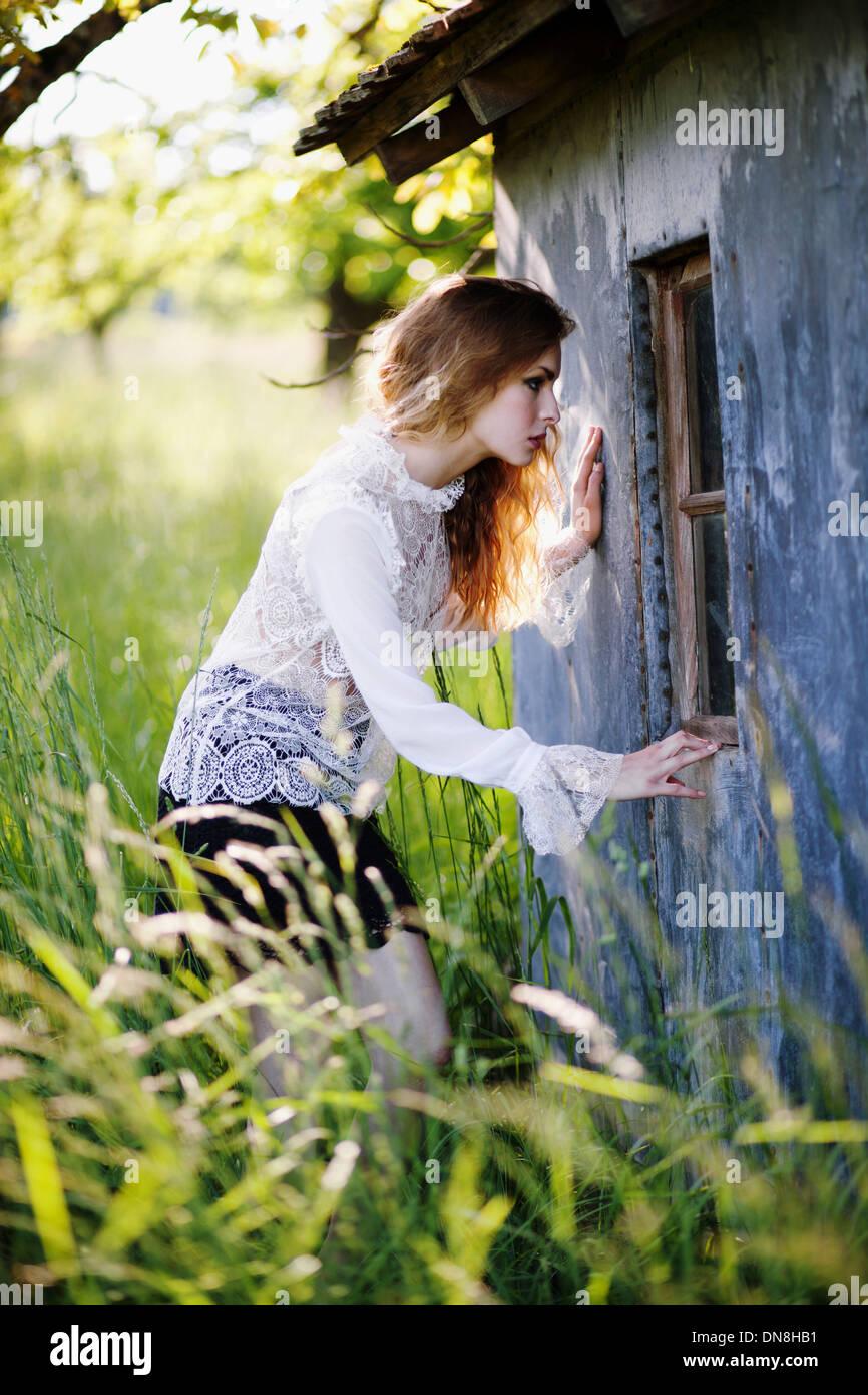 Junge Frau schaut in das Fenster einer Hütte Stockfoto
