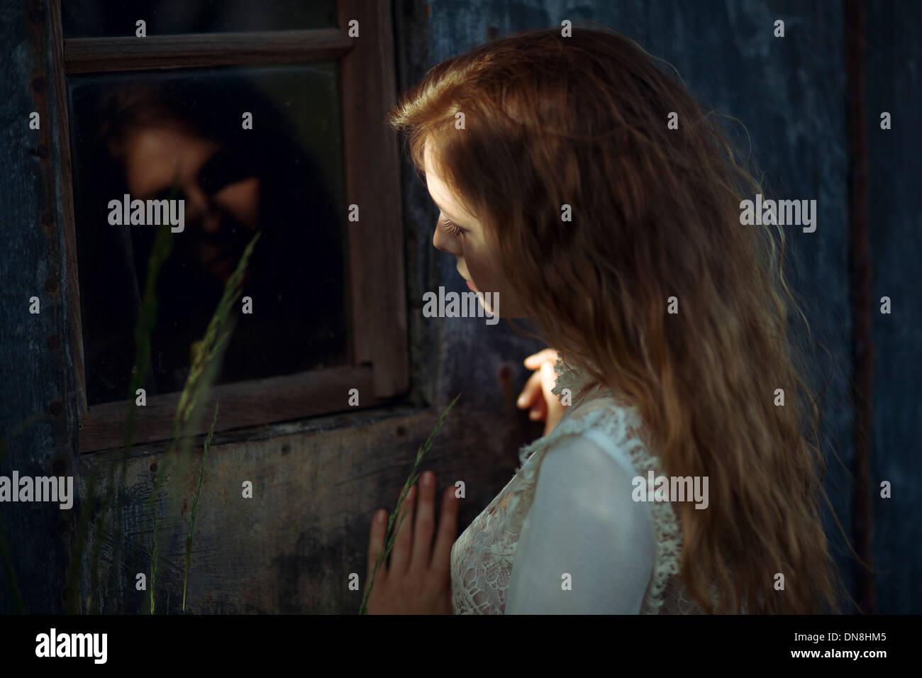 Junge Frau mit Spiegelbild im Fenster Stockbild