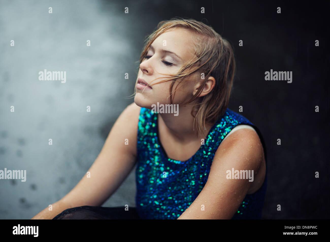 Junge Frau sitzt im Regen auf der Straße Stockbild