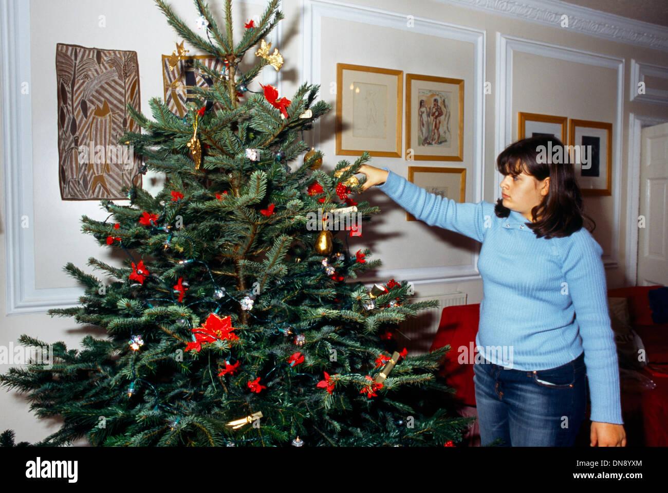 Weihnachtsbaum England.Mädchen Tragen Pullover Und Jeans Dekorieren Weihnachtsbaum England