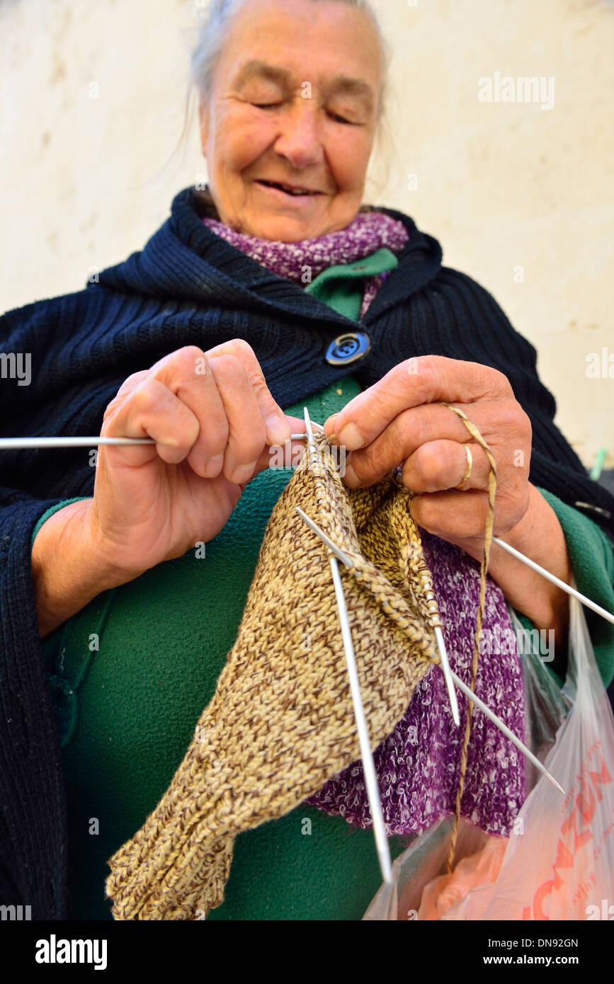 Alte Dame stricken mit echter Wolle in ?ibenik Marktplatz, Kroatien, die Kleidungsstücke sind dann für den Verkauf Stockbild