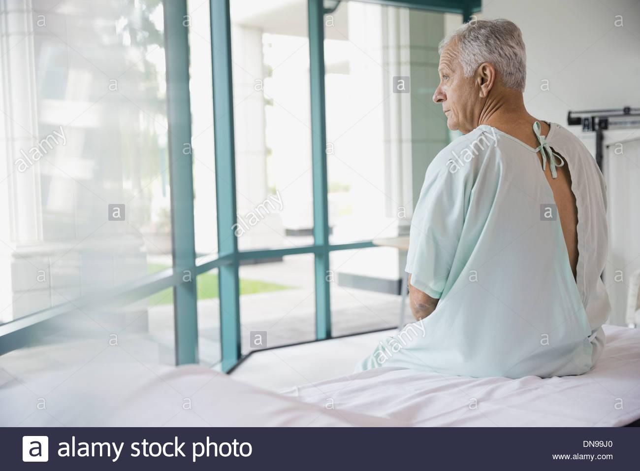 Nachdenklich senior Patient sitzt am Krankenhausbett Stockbild