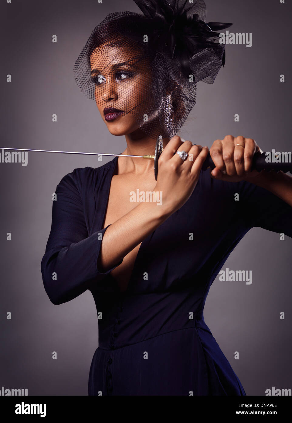 Schöne schwarze Frau mit einem Schleier ein Katana Schwert in ihren Händen hält Stockfoto