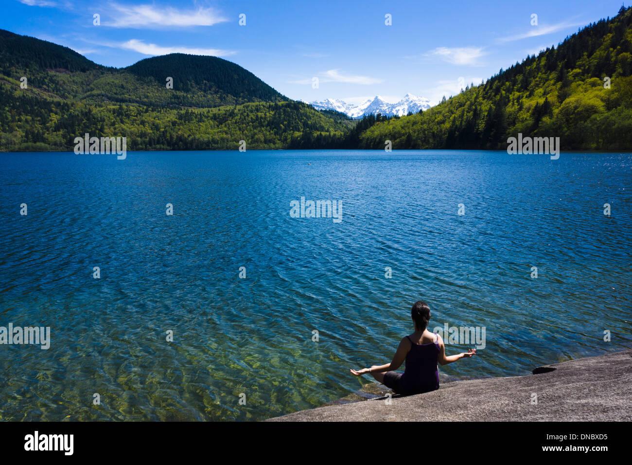 Junge Frau meditieren am Hicks Lake in Sasquatch Provincial Park, Britisch-Kolumbien, Kanada Stockbild