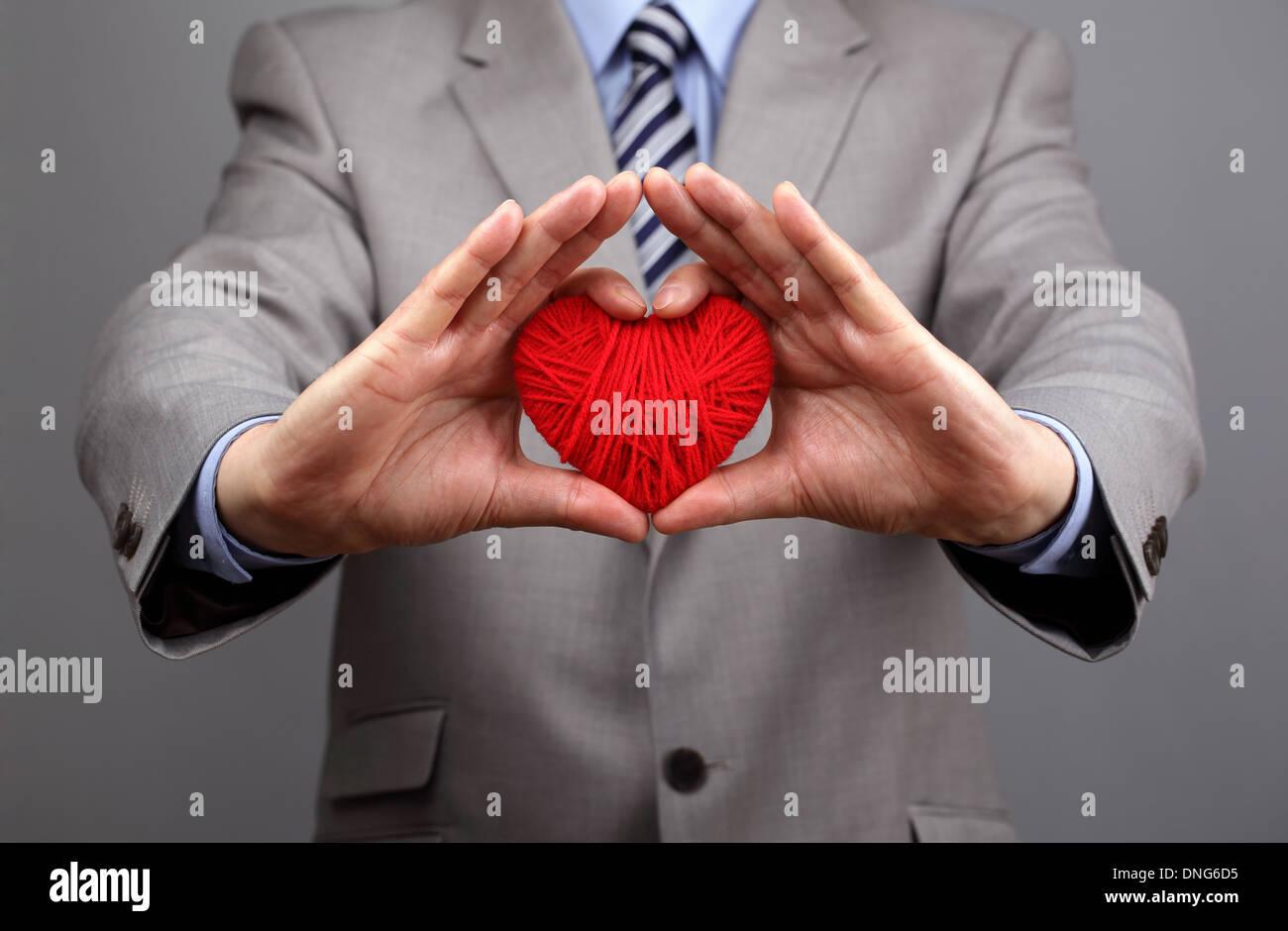 Geschäftsleute hält sich ein rotes Herz Stockbild