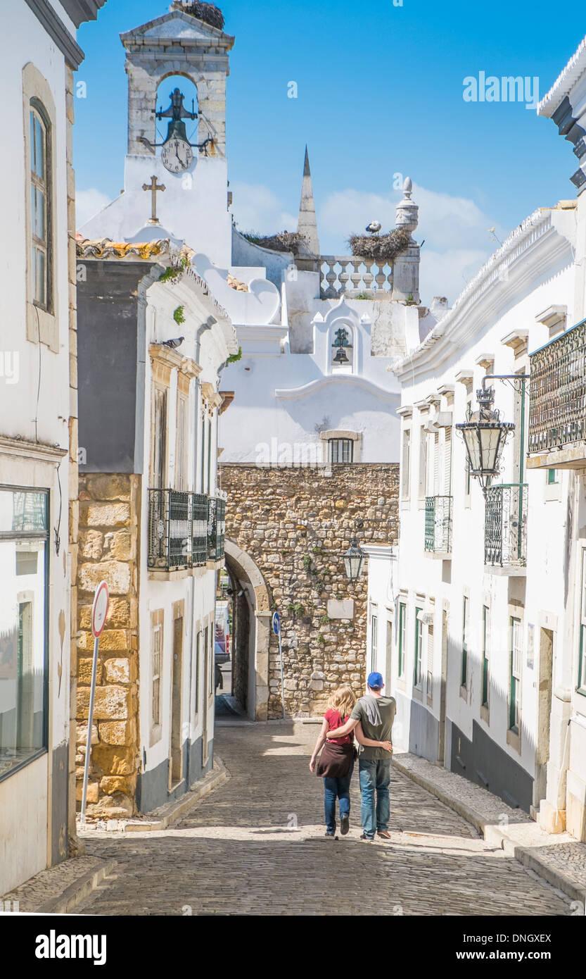 junges Paar auf einer Straße mit Kopfsteinpflaster in der Altstadt von Faro, Algarve, portugal Stockbild