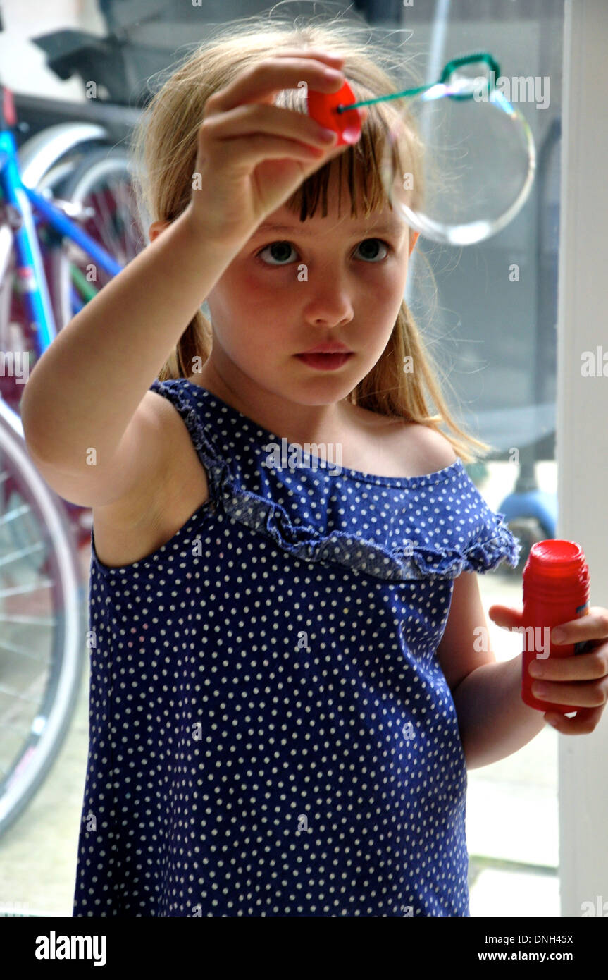 kleine blonde Mädchen Uhren eine Blasenbildung, wie sie Luftblasen bläst Stockbild