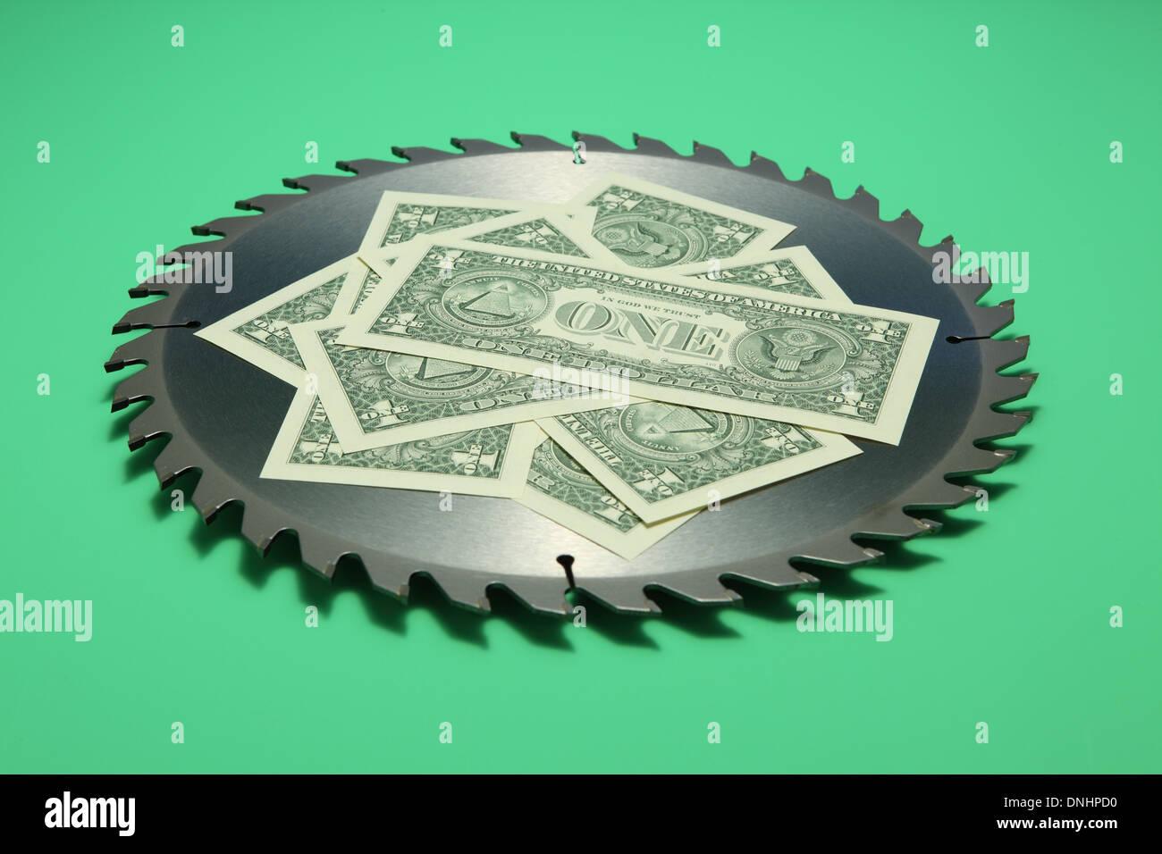 Eine scharfe Runde Metall Sägeblatt mit US-Währung auf grünem Hintergrund. Stockbild