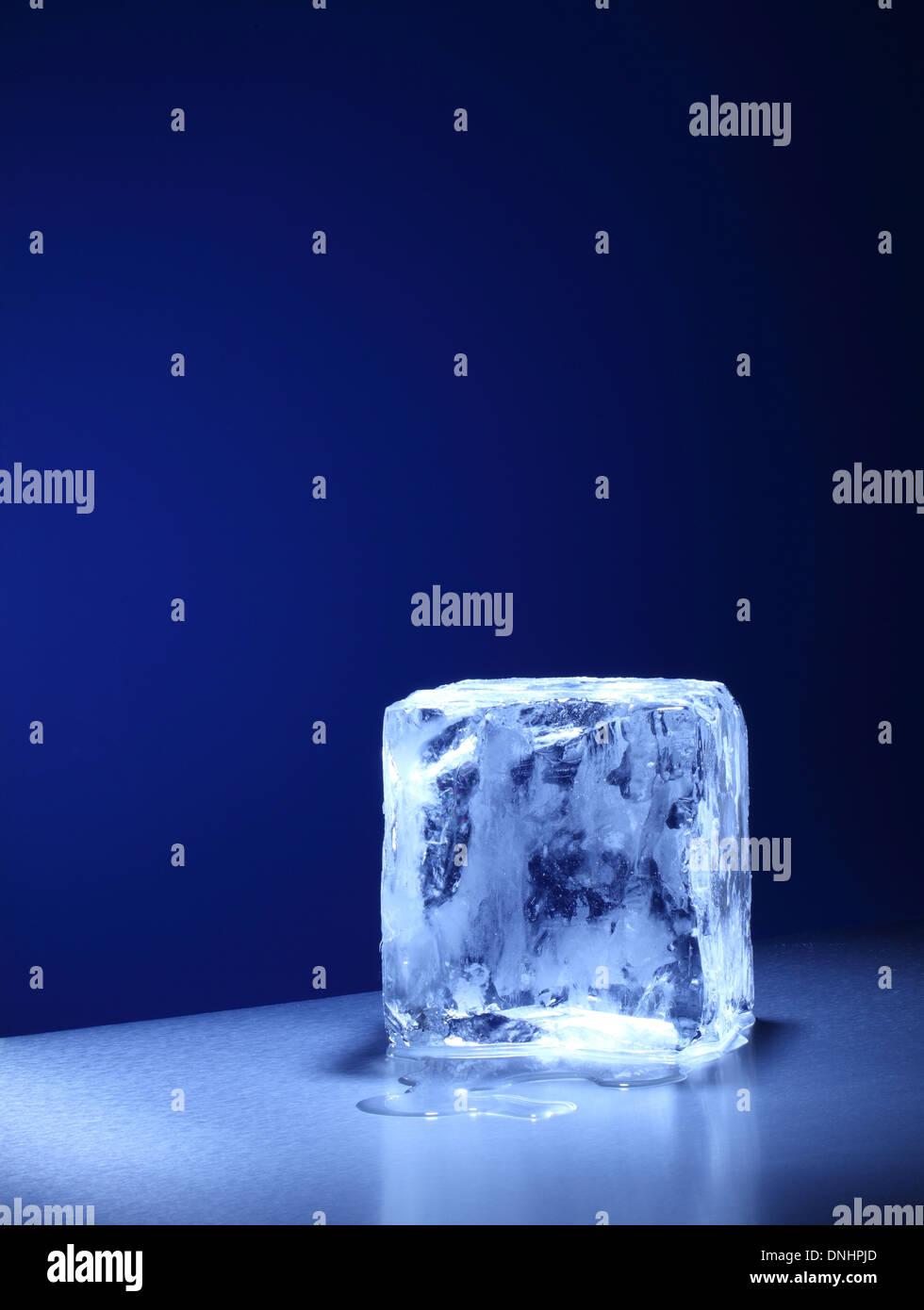 Ein großer quadratischer Würfel / Eisblock langsam schmelzen. Stockbild