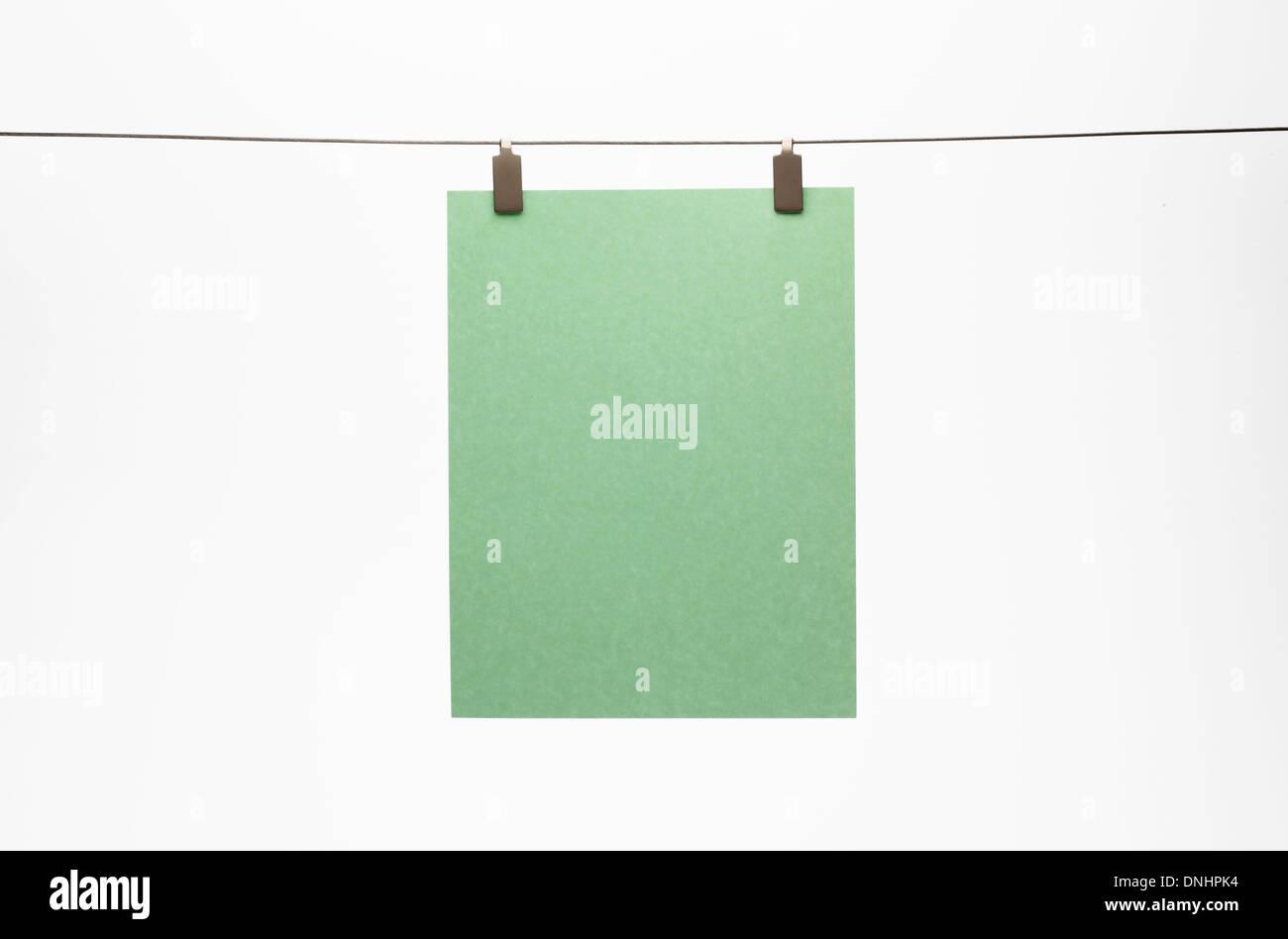 Ein leeres Blatt grün Papier mit einem Clip zu einem geraden Draht hängen. Weißem Hintergrund Stockbild