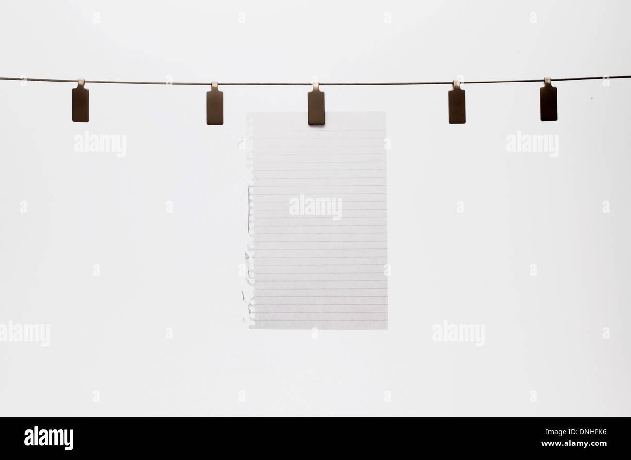 Ein leeres Blatt Papier mit einem Clip zu einem geraden Draht hängen. Weißem Hintergrund Stockbild