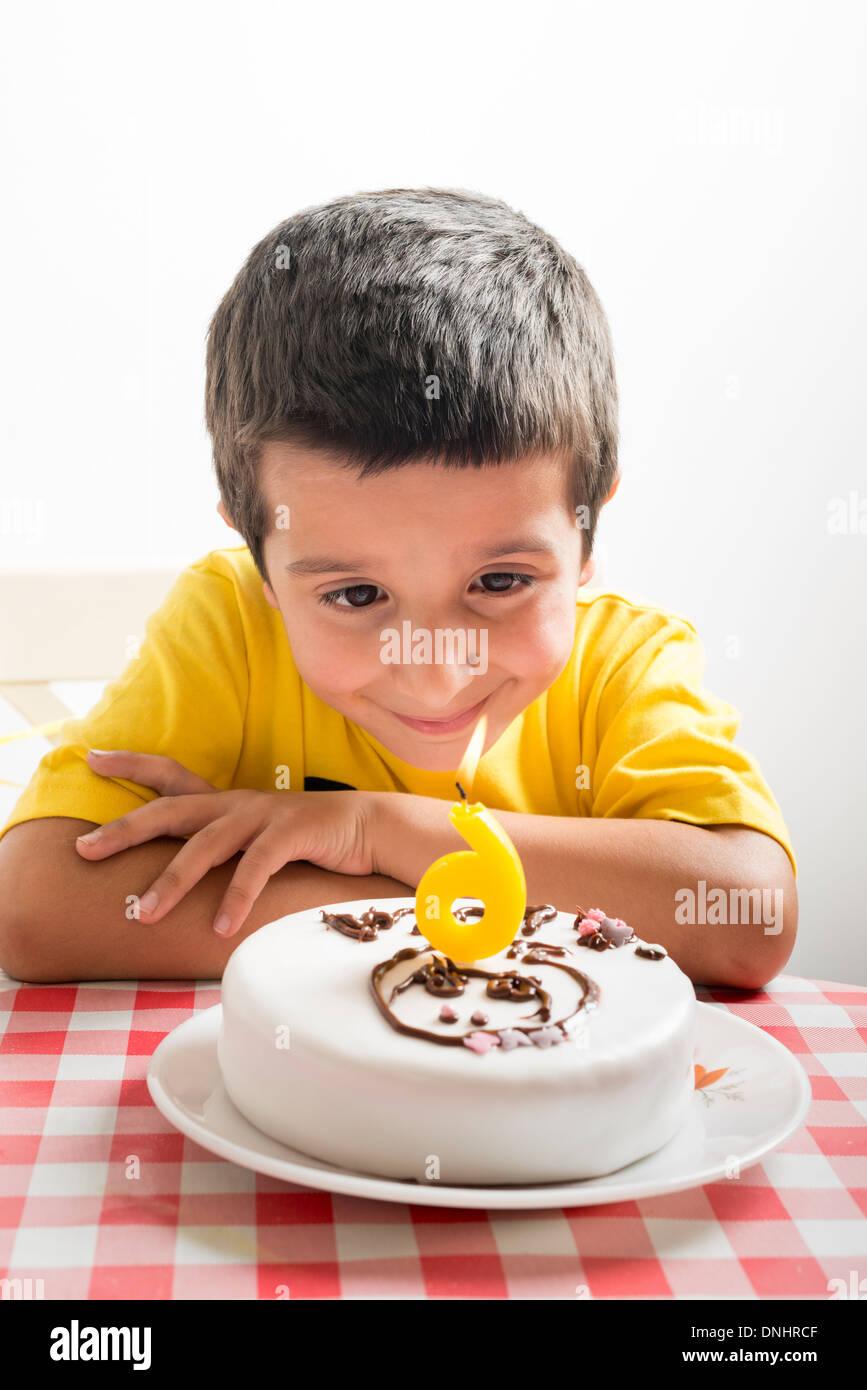 Sechs Jahre alter Junge schaut Geburtstagstorte Stockfoto
