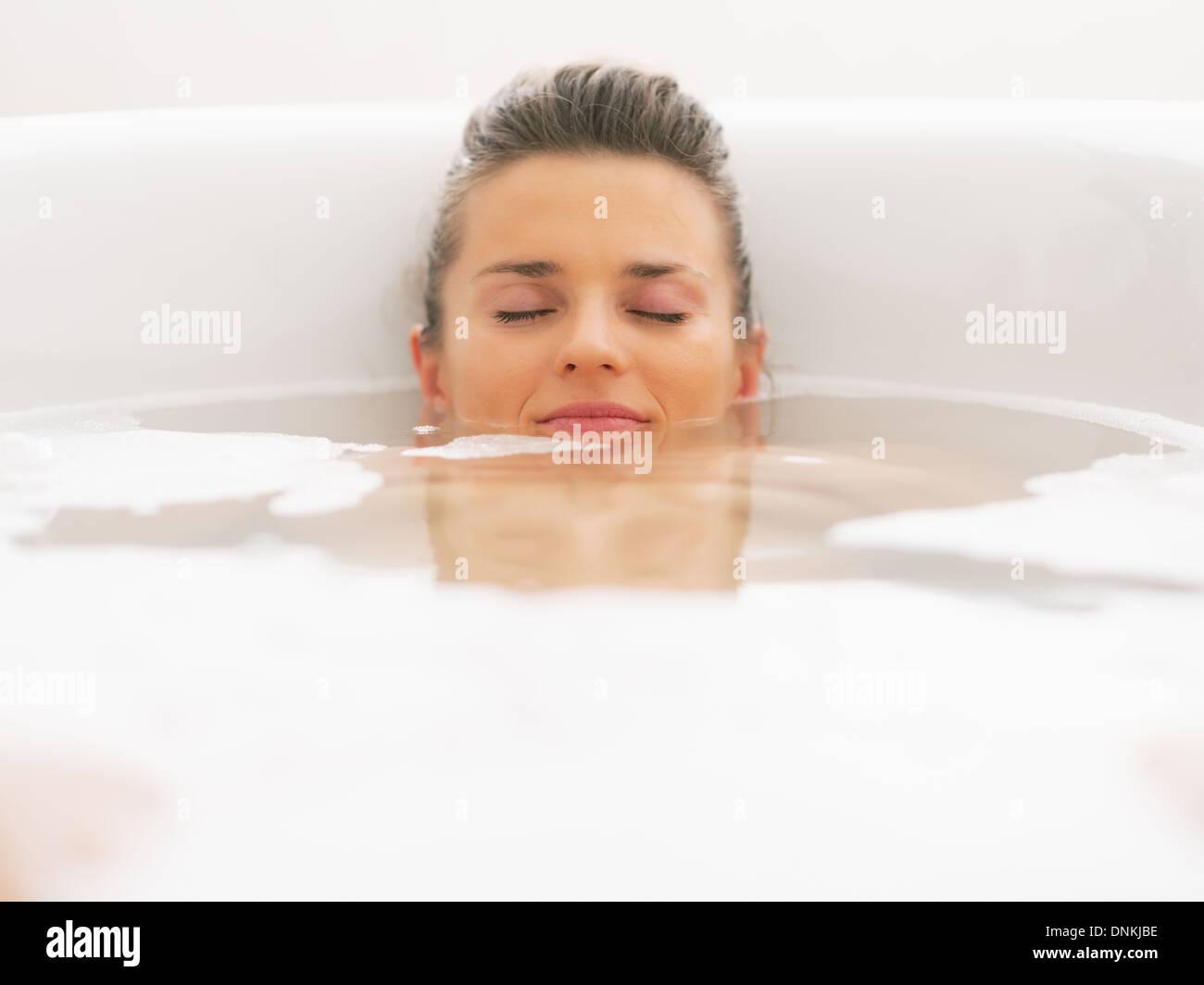 Junge Frau, die Verlegung unter Wasser in Badewanne Stockbild