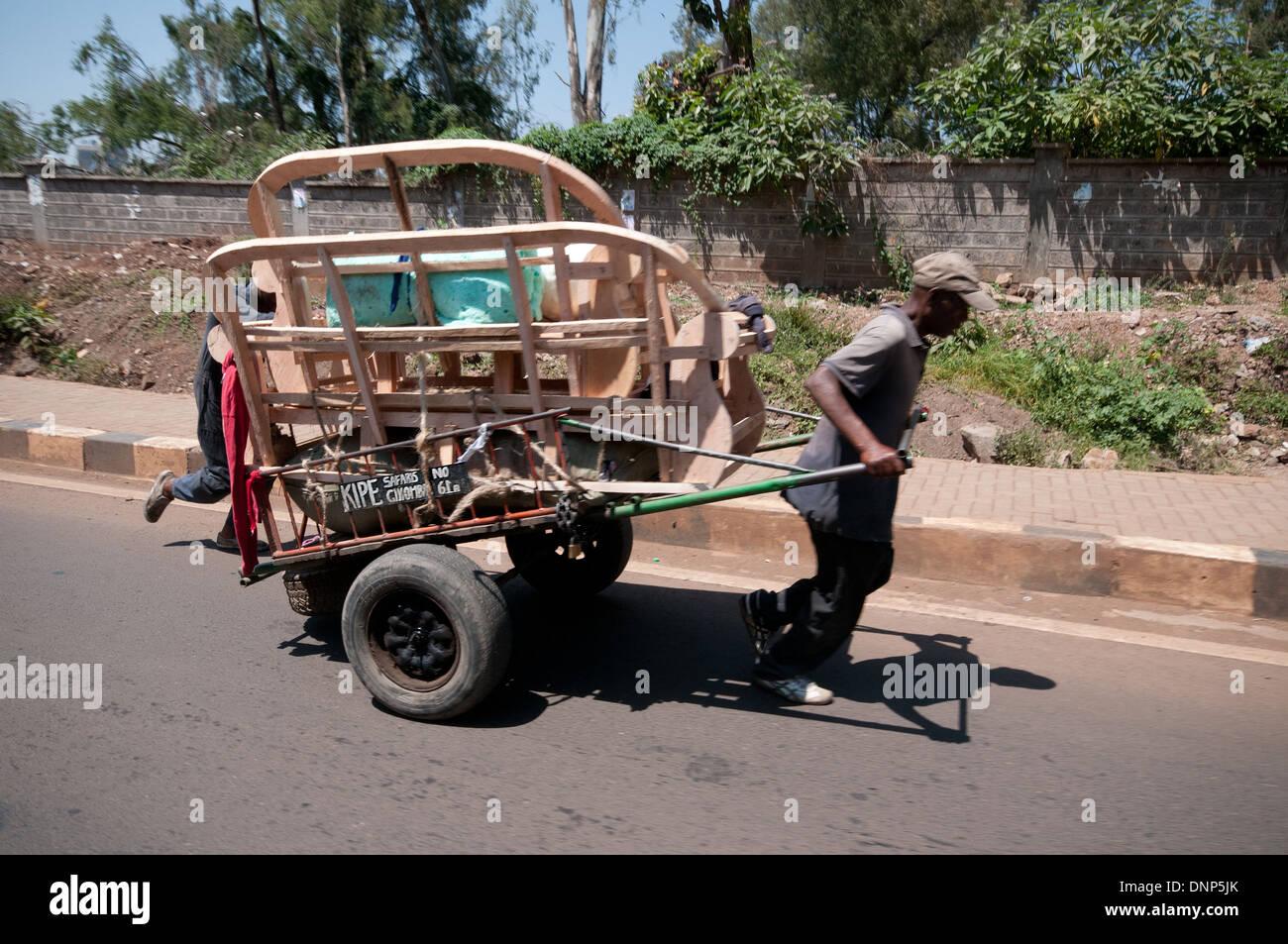 Männer kämpfen mit schwer beladenen Wagen mit Möbeln auf Wald Nairobi Kenia NAIROBI Kenia TROLLEY CART Straßenverkehr Stockbild