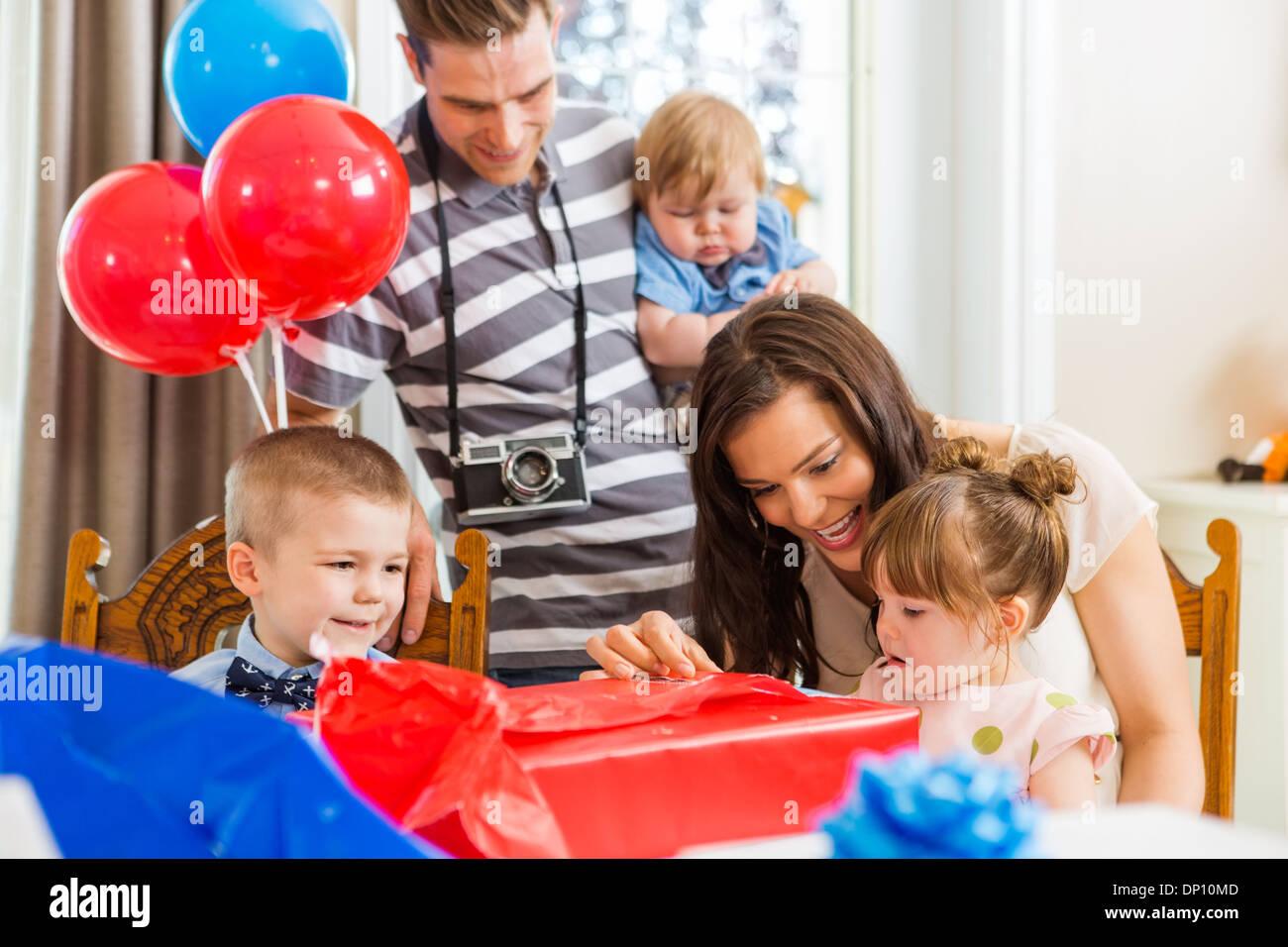 Familie öffnen Geburtstagsgeschenk zu Hause Stockbild