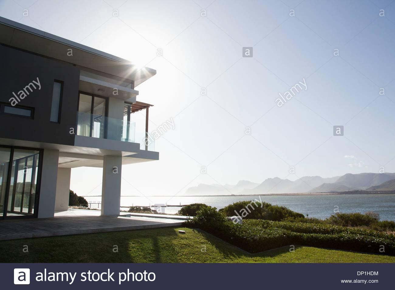 Sonne, See und modernes Haus Stockbild