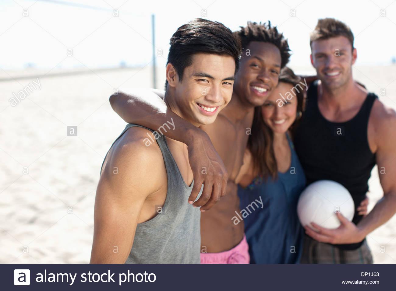 Vier Personen stehen am Beach-Volleyballplatz Stockbild