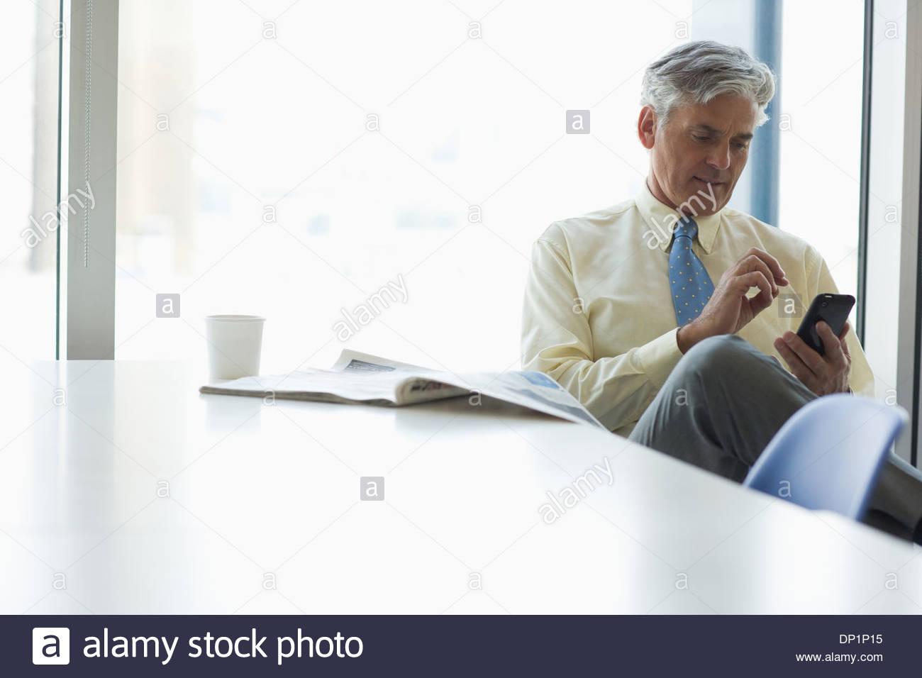 Geschäftsmann SMS auf Handy in cafeteria Stockbild
