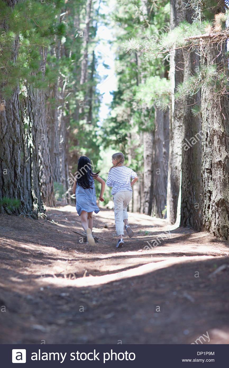 Zwei Mädchen im Wald laufen Stockbild