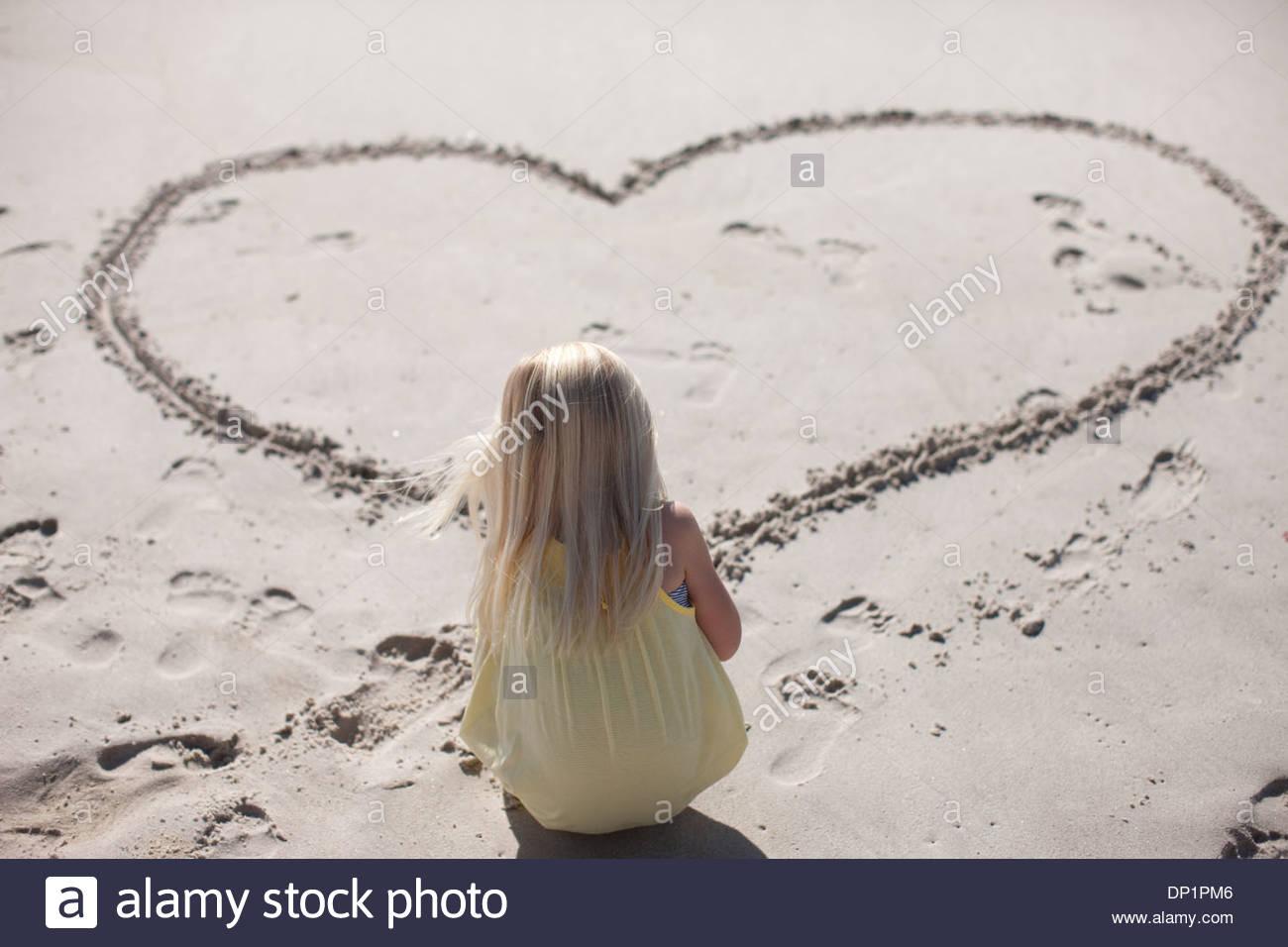 Mädchen Zeichnung Herz im Sand am Strand Stockbild