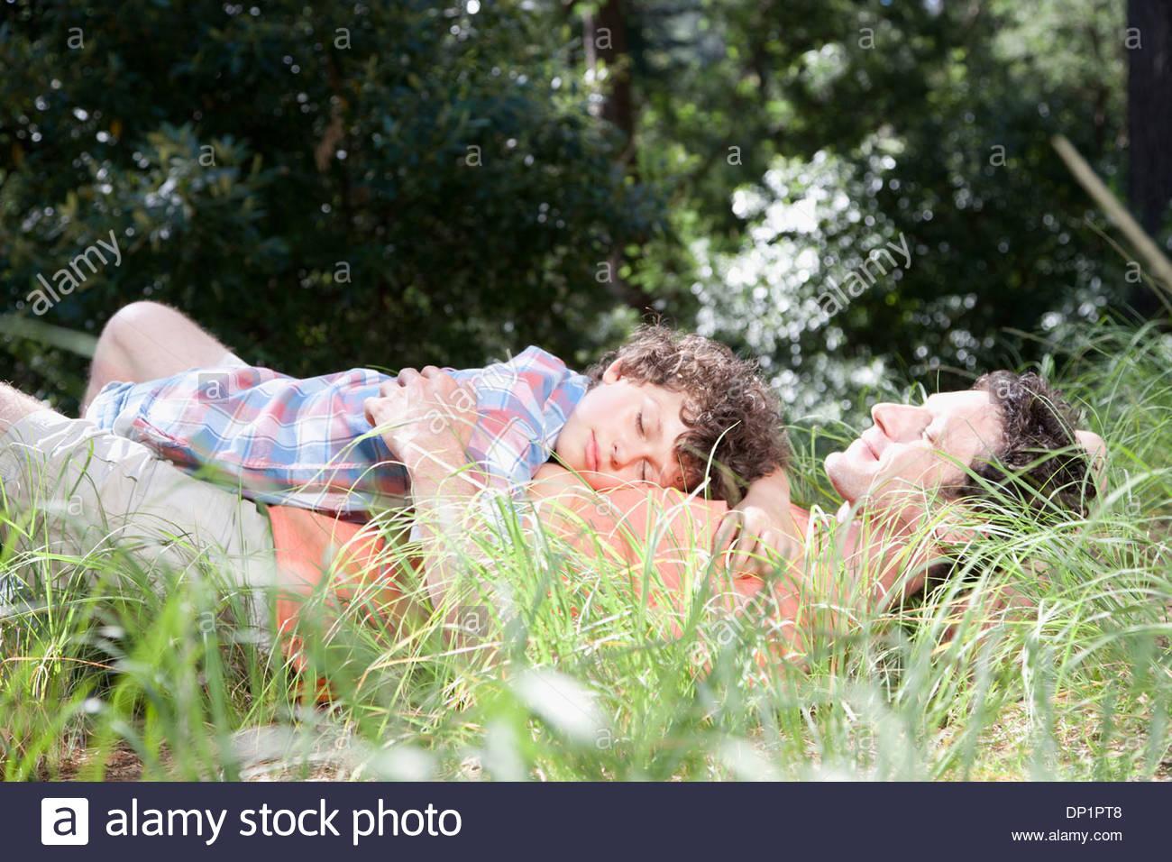 Vater und Sohn schlafen im Rasen Stockbild