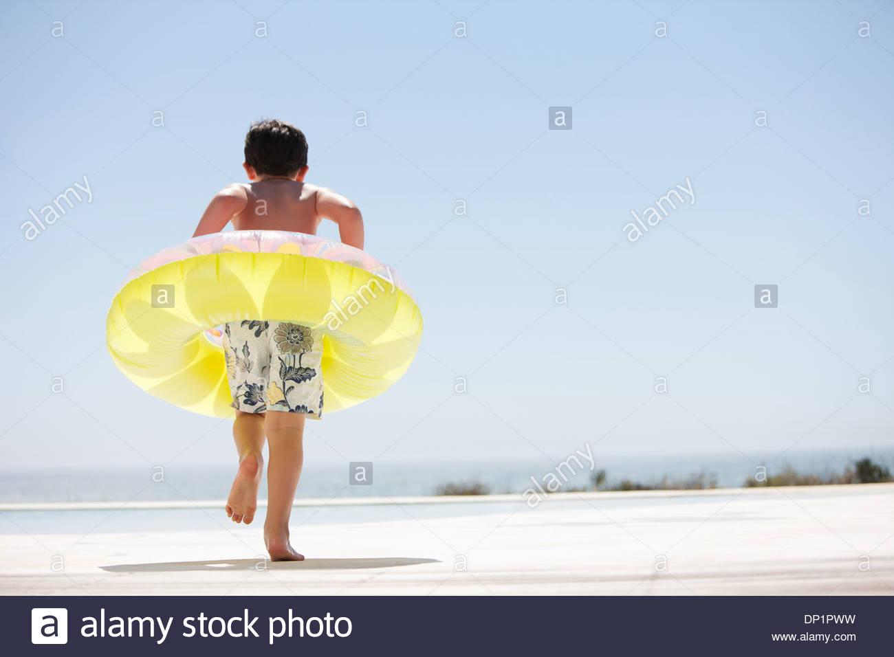 Junge mit aufblasbaren Ring heraustreten aus Infinity-pool Stockbild