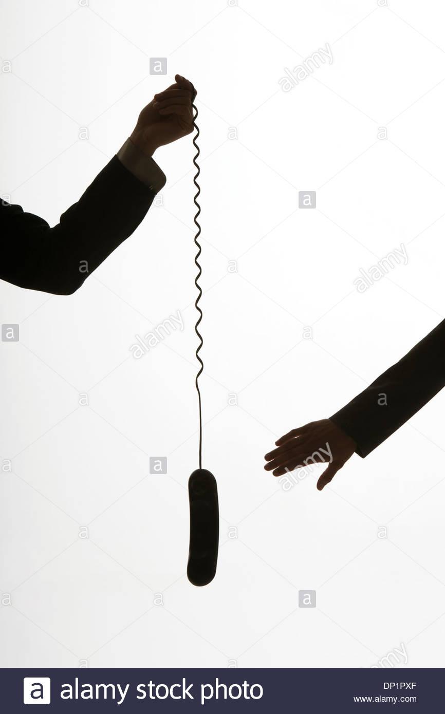 Zwei Arme, vorbei an ein Telefon Stockbild