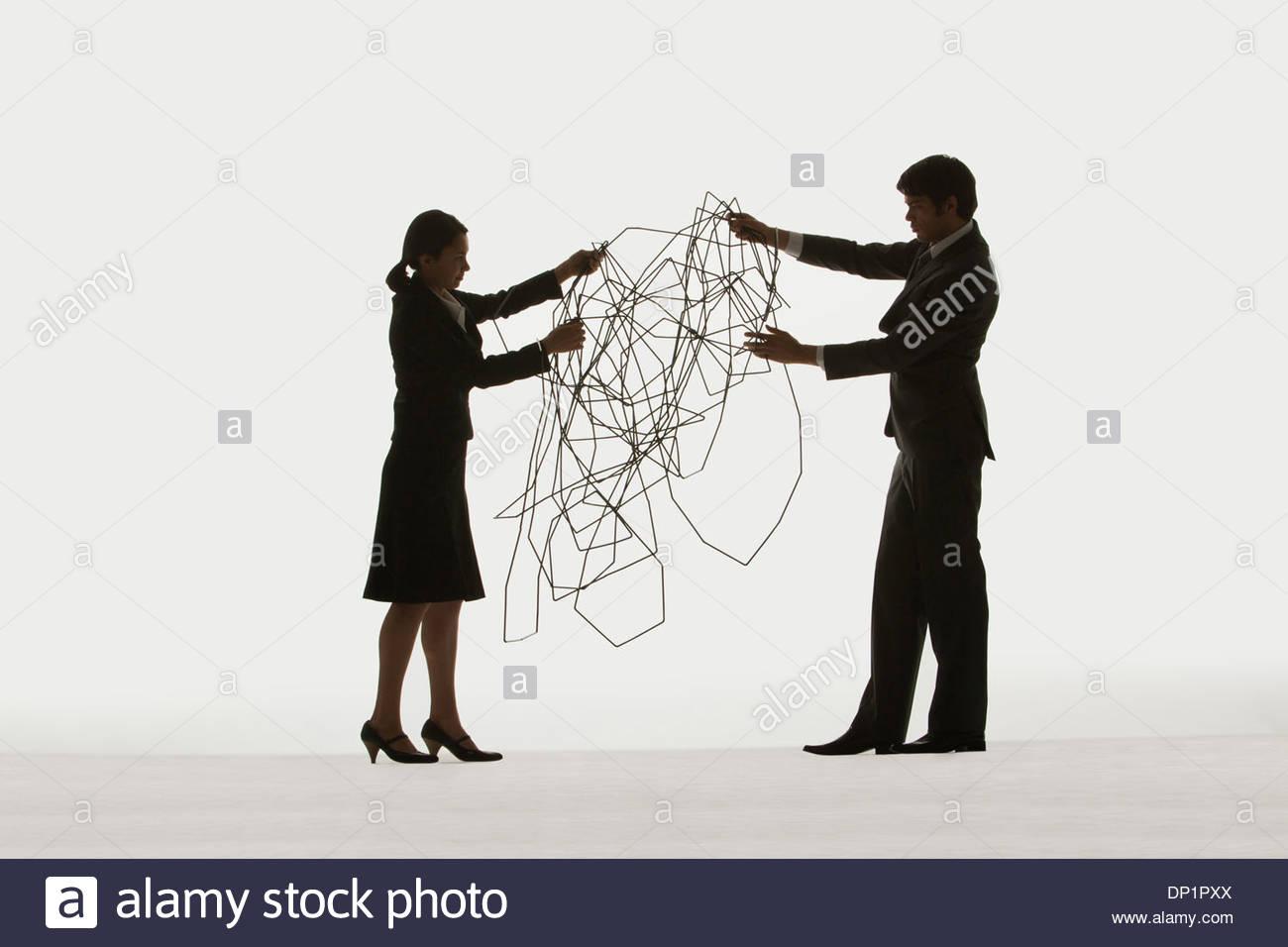 Zwei Geschäftsleute halten ein Kabel Stockbild