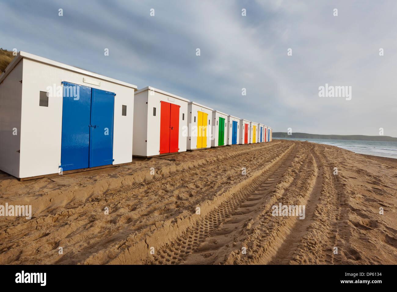 Strandhütten in einer Reihe auf Woolacombe Sands in North Devon, UK. Stockbild