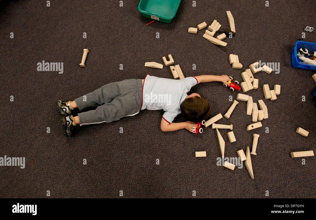 Junge spielt mit Holz Blöcke auf dem Boden in der Vorschule Stockbild