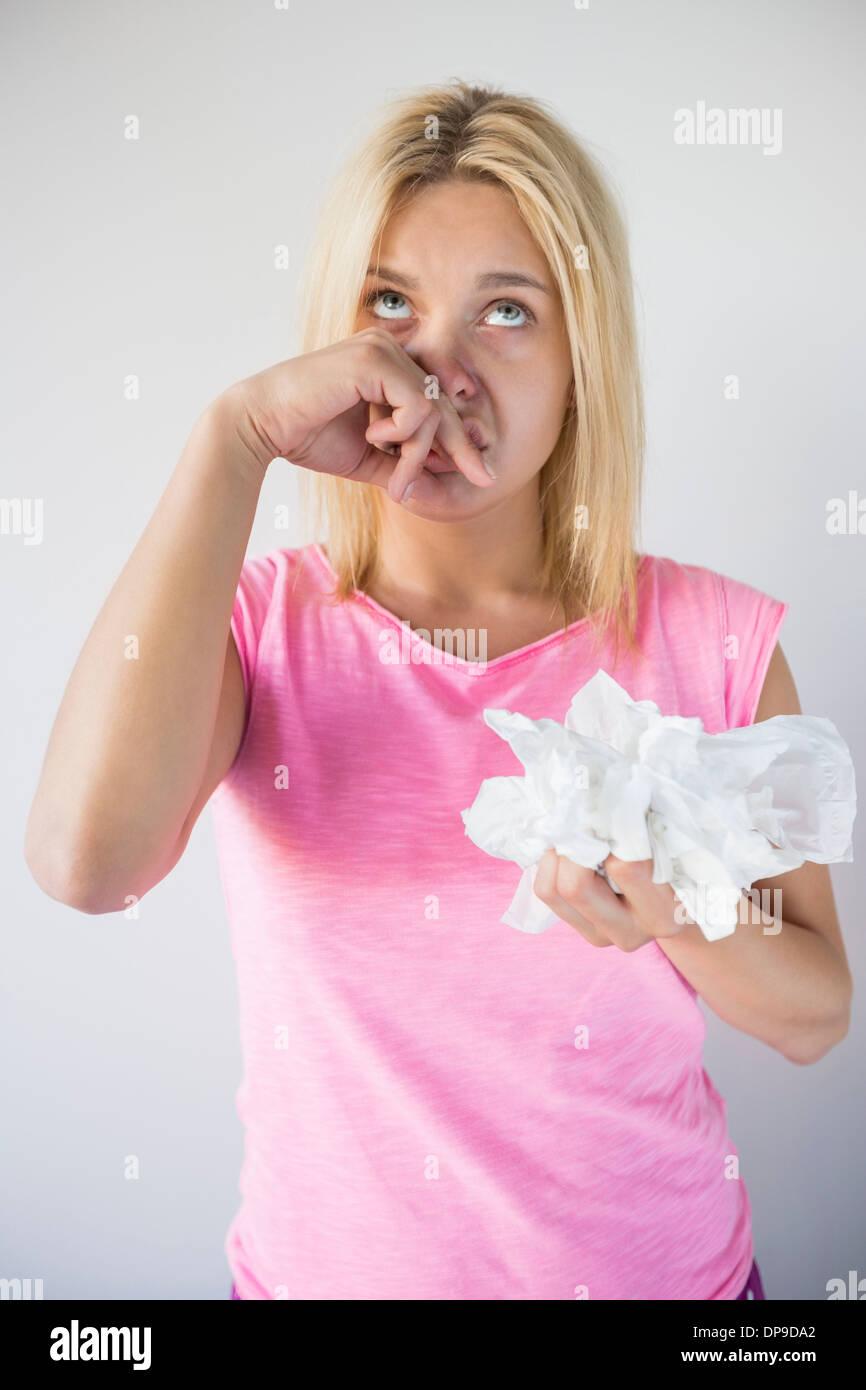 Junge Frau leidet Kälte halten Tissue-Papiere vor grauem Hintergrund Stockbild